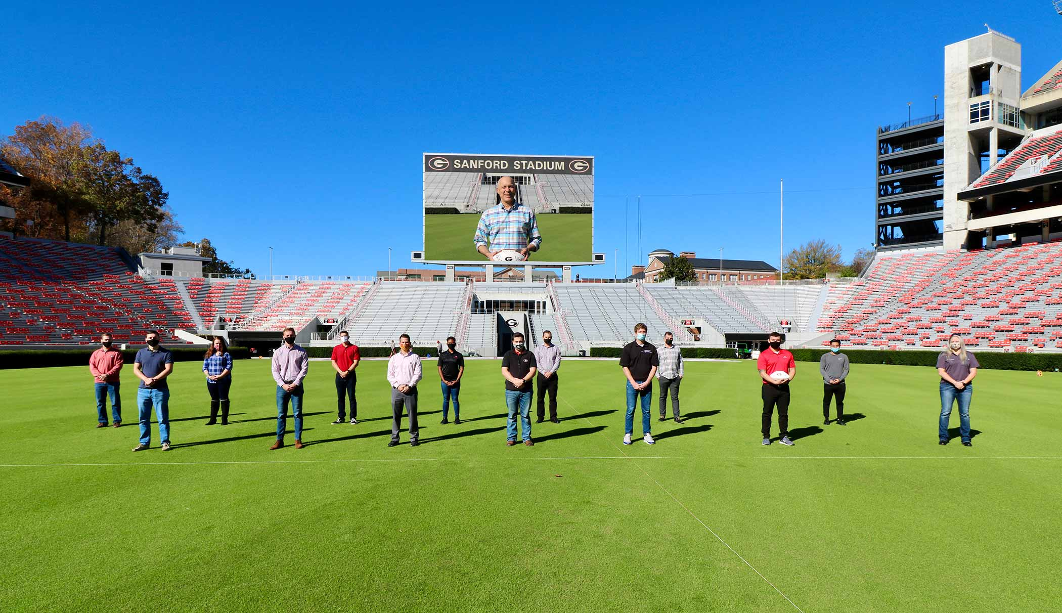 Ted Barco, Director of the Student Veterans Resource Center, standing with some UGA student veterans on the football field in Sanford Stadium.